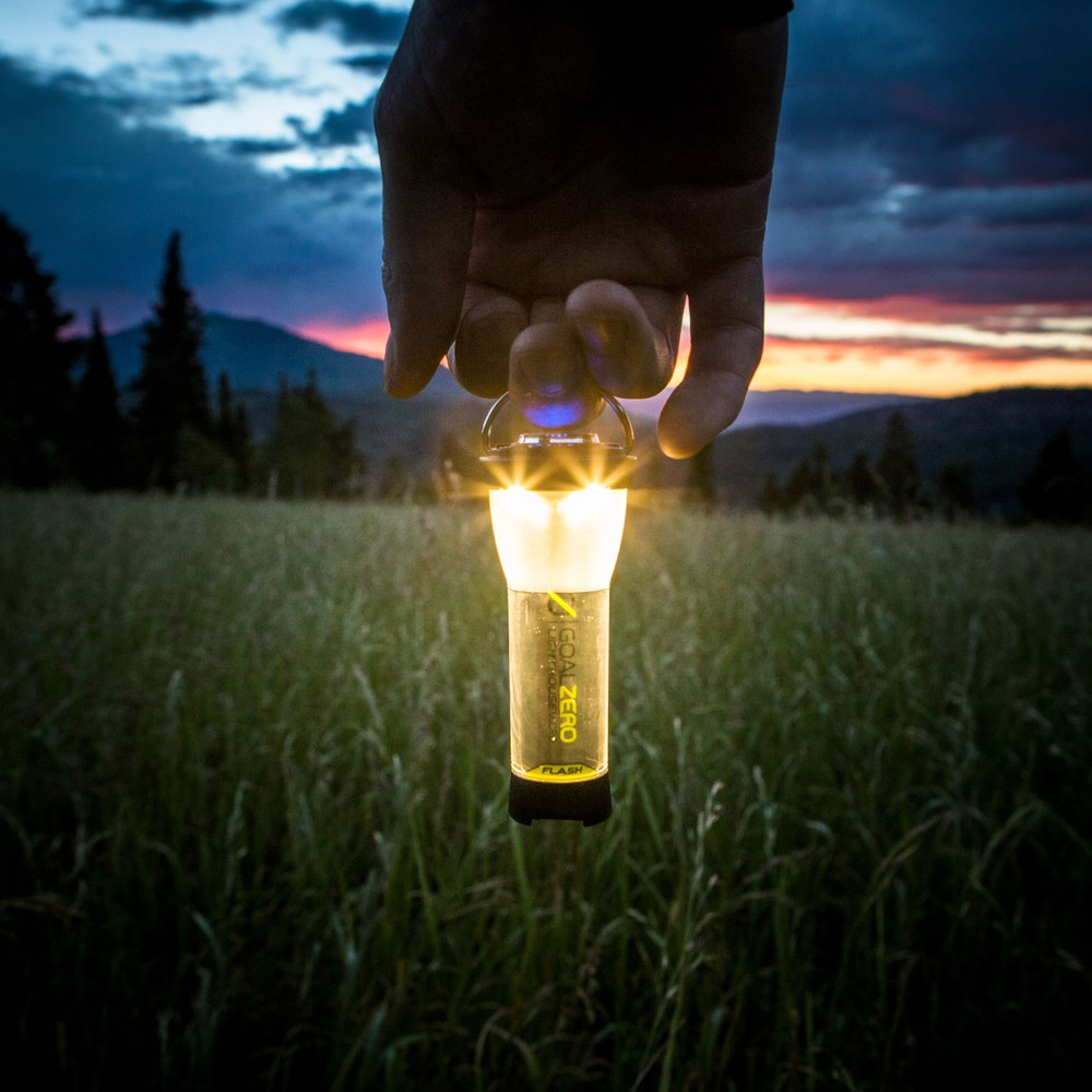 Lighthouse Micro Flash USB Rechargeable - Held with Sunset Lit in Grass